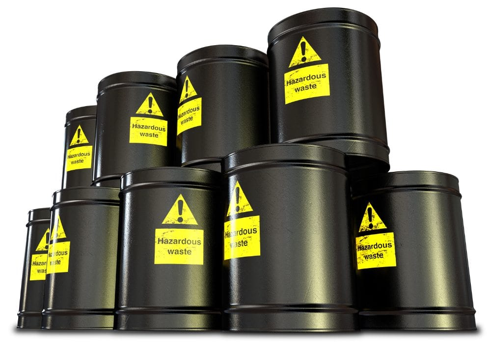 A stack of black metal barrels with yellow hazardous waste drum labels on each