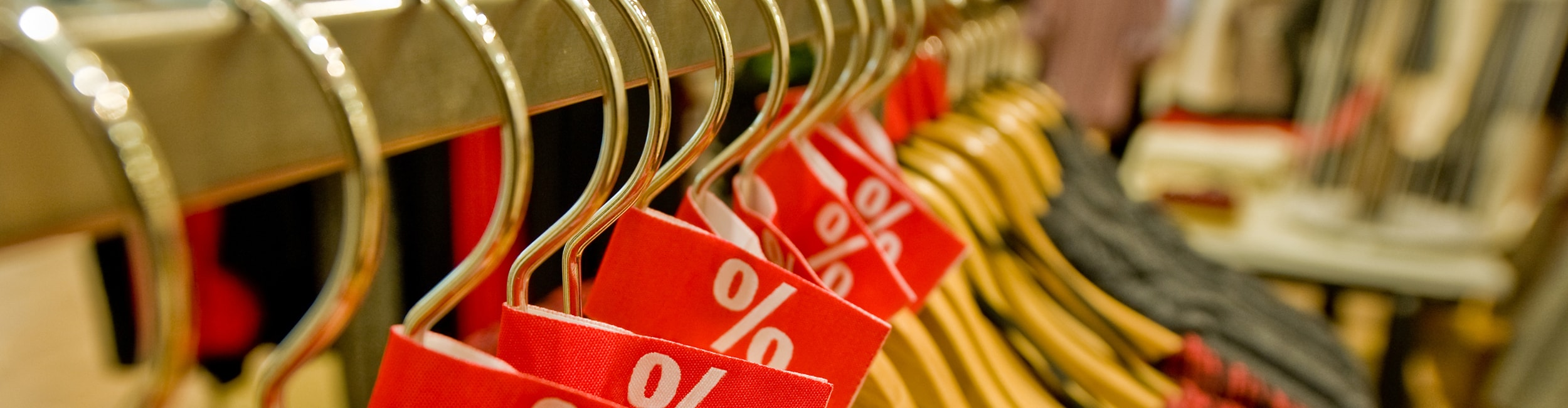 Clothes on a hanger with percent sales signs.